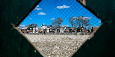 Residential houses are seen through a hole of a construction site fence in Queens on a sunny day on March 18, 2019 in New York City. (Photo by Johannes EISELE / AFP)        (Photo credit should read JOHANNES EISELE/AFP via Getty Images)