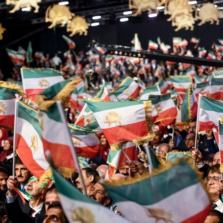 TOPSHOT - Mujahedin-e Khalq members waves Iranian flags during the conference