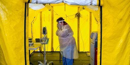 NEWTON, MA - MARCH, 16: Nurse practitioner Amy Israelian puts on protective gear in a tent in the parking lot of the Newton-Wellesley Hospital before testing a possible coronavirus patient in Newton, MA on March 16, 2020. (Photo by Adam Glanzman/For The Washington Post via Getty Images)