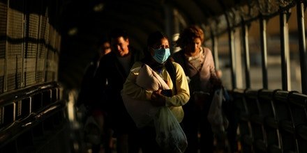 A woman wearing a protective mask carries her baby as she walks towards El Paso, Texas, U.S. at the international border bridge Paso del Norte, as seen from Ciudad Juarez, Mexico March 13, 2020. REUTERS/Jose Luis Gonzalez - RC2FJF9C7OTW