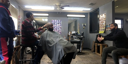 Jackson Mayor Chokwe Antar Lumumba, right, talks to employees and customers, including barber Ron Davis, second from left, at the Head Turners Barbershop in Jackson, Miss., on March 7, 2020.