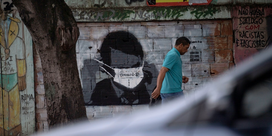 A man walks past a graffiti of Brazilian President Jair Bolsonaro wearing a face mask in downtown Rio de Janeiro, Brazil, on March 24, 2020 during the coronavirus COVID-19 pandemic. - The Rio de Janeiro state government is requesting people not to go to the beach or any other public areas as a measure to contain the coronavirus pandemic. (Photo by Mauro PIMENTEL / AFP) (Photo by MAURO PIMENTEL/AFP via Getty Images)