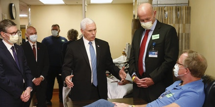 Vice President Mike Pence, center, visits a patient who survived the coronavirus and was going to give blood during a tour of the Mayo Clinic Tuesday, April 28, 2020, in Rochester, Minn. as he toured the facilities supporting COVID-19 research and treatment. (AP Photo/Jim Mone)