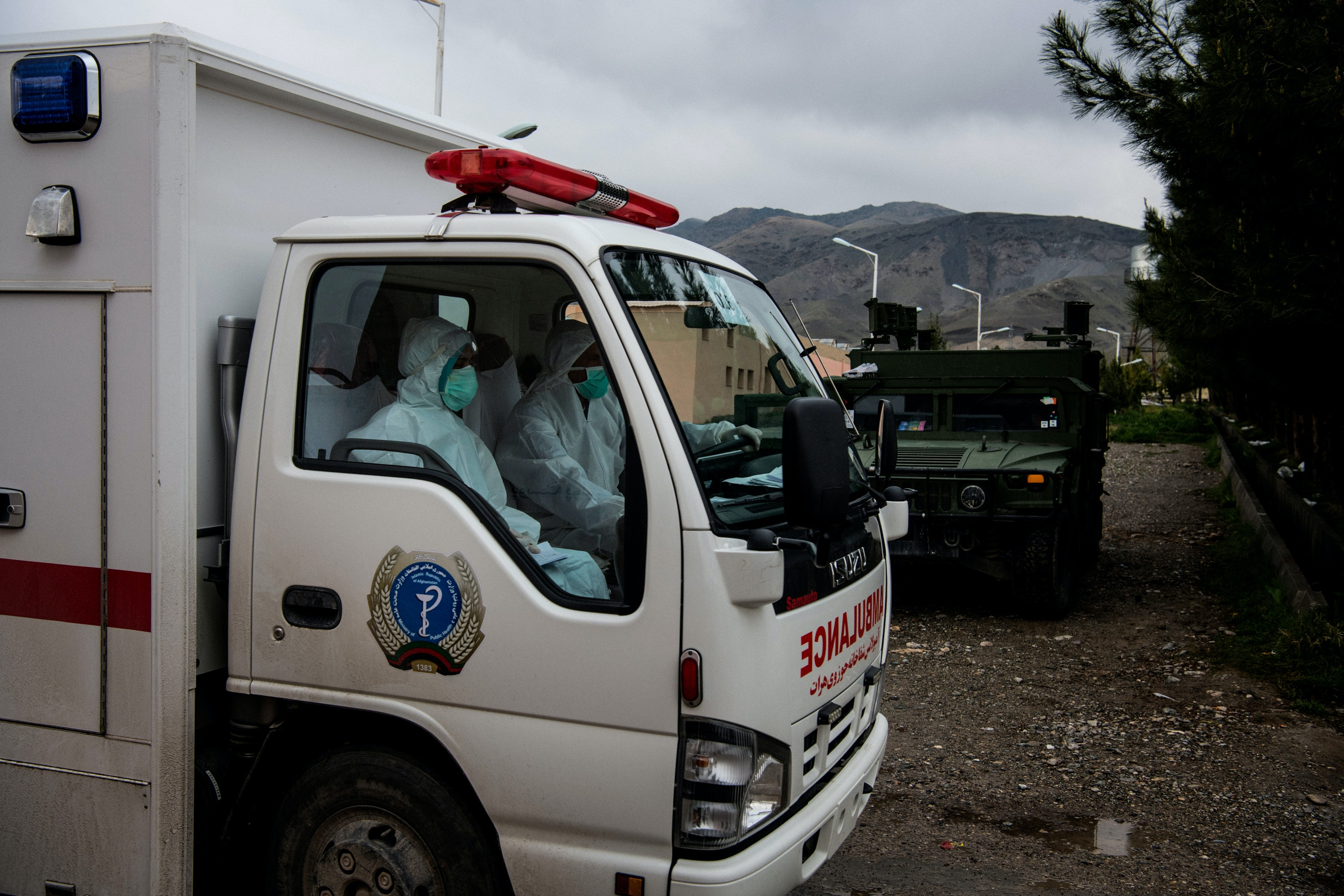 An ambulance, it's driver and passenger wearing head-to-toe protective equipment, departs a paediatric hospital which was recently repurposed as Herat's primary isolation facility for coronavirus in the early days of the coronavirus outbreak in Afghanistan. On this day, the country had an official count of 71 positive coronavirus cases.