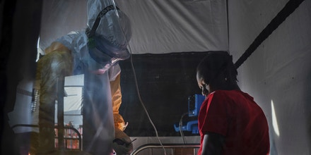 In this Saturday, July 13, 2019 photo, health workers wearing protective gear check on Ivette Adania, 24, a mother of four whose husband died of Ebola, at an Ebola treatment center in Beni, Congo. More than 1,700 people in eastern Congo have died as the virus has spread in areas too dangerous for health teams to access. (AP Photo/Jerome Delay)