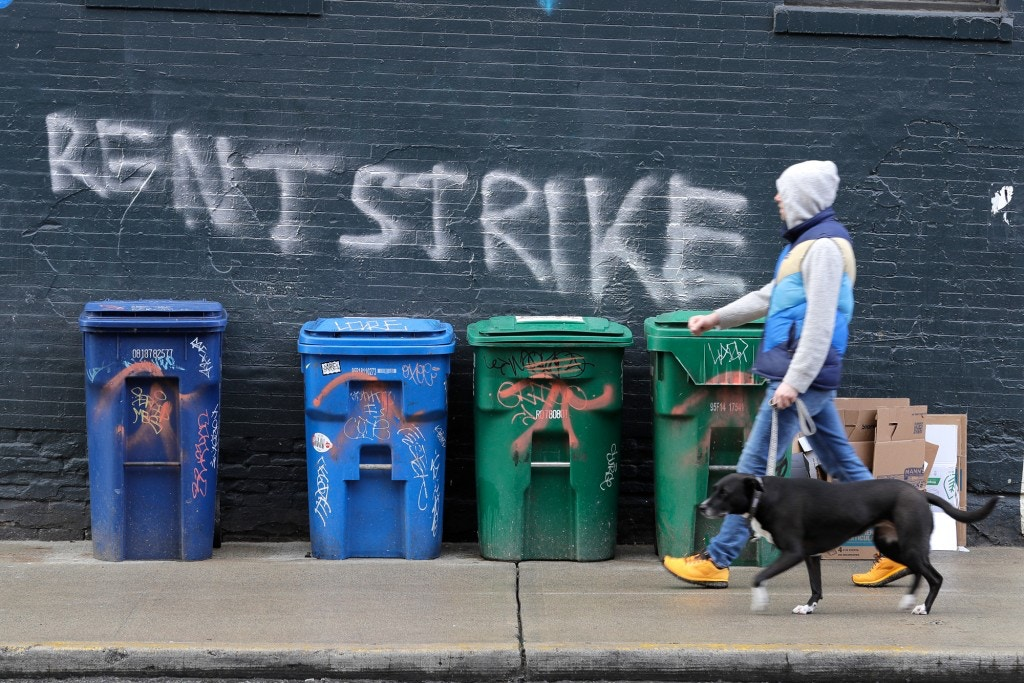 "A pedestrian walks past graffiti that reads ""Rent Strike"" Wednesday, April 1, 2020, in Seattle's Capitol Hill neighborhood. With millions of people suddenly out of work and rent due at the first of the month, some tenants in the U.S. are vowing to go on a rent strike until the new coronavirus pandemic subsides. Some cities have temporarily banned evictions, but advocates for the strike are demanding that rent payments be waived, not delayed, for those in need during the crisis. (AP Photo/Ted S. Warren)"