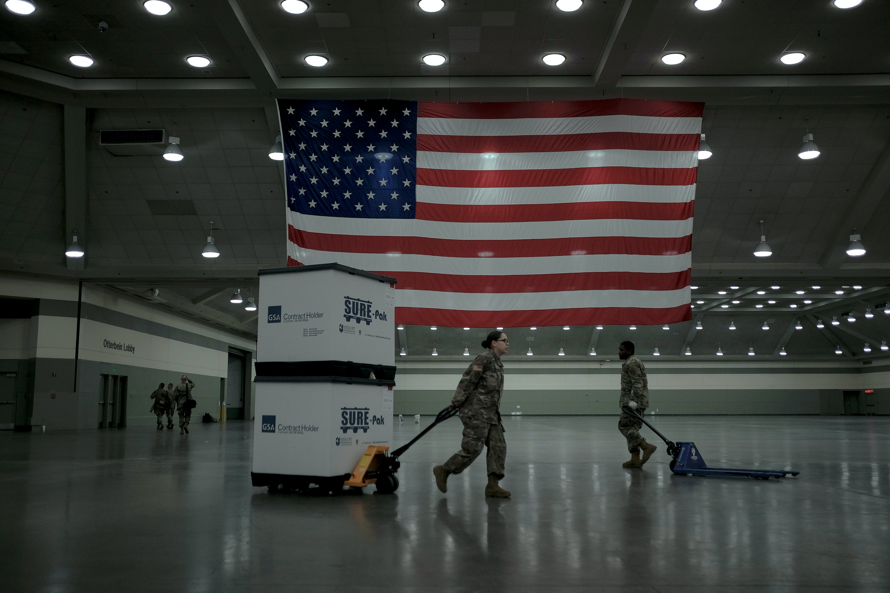 Members of the Maryland National Guard unload crates of beds from FEMA into the convention center in Baltimore, Md., on March 28, 2020. The Guard set up a 250-bed field hospital in preparation for Covid-19 patients.