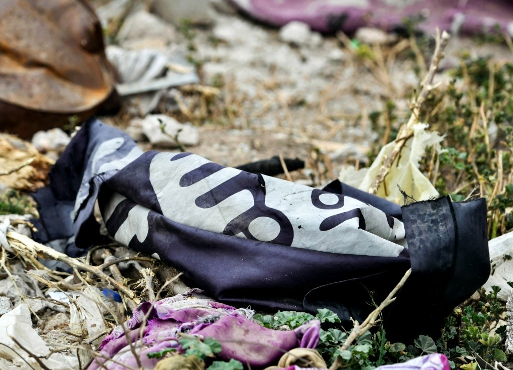 "This picture taken on March 24, 2019 shows a discarded Islamic State (IS) group flag lying on the ground in the village of Baghouz in Syria's eastern Deir Ezzor province near the Iraqi border, a day after IS group's ""caliphate"" was declared defeated by the US-backed Kurdish-led Syrian Democratic Forces (SDF)."