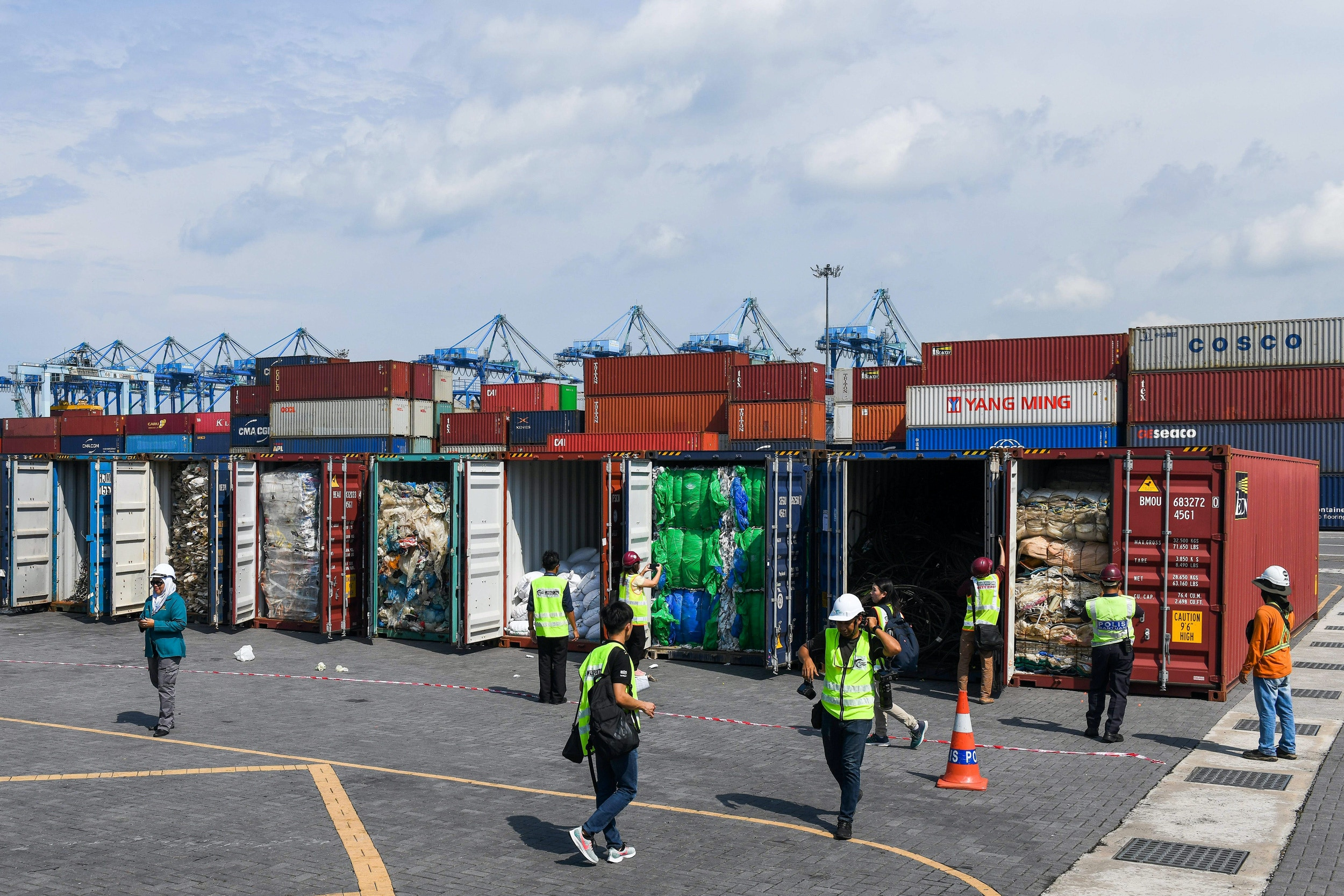 Malaysian officials and journalists inspect containers filled with plastic waste shipment before sending back to the country of origin in Port Klang, west of Kuala Lumpur on May 28, 2019. (Photo by Mohd RASFAN / AFP)        (Photo credit should read MOHD RASFAN/AFP via Getty Images)
