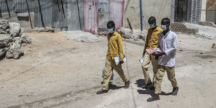Students walk in a Mogadishu neighbourhood wearing face masks as protective measure against Coronavirus on Thursday March 19, 2020. - Somali prime minister on Wednesday announced closure of schools and universities as a protective measure against Convid-19. (Photo by Abdirazak Hussein FARAH / AFP) (Photo by ABDIRAZAK HUSSEIN FARAH/AFP via Getty Images)