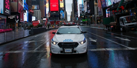 A NYPD car drives by Times Square as rain falls on March 28, 2020 in New York City. - US President Donald Trump said on March 28, 2020 that he's considering a short-term quarantine of New York state, New Jersey, and parts of Connecticut. (Photo by Kena Betancur / AFP) (Photo by KENA BETANCUR/AFP via Getty Images)