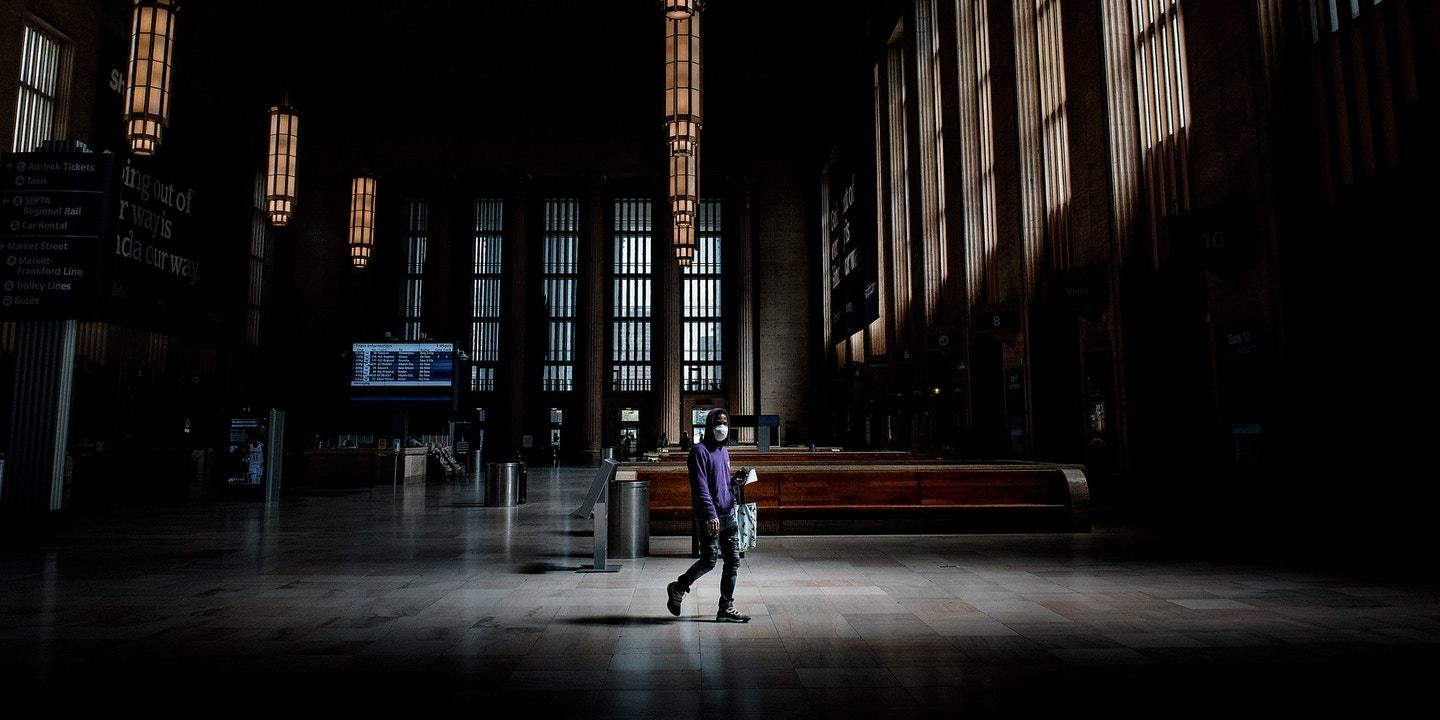 A man wearing a protective mask walks through an almost empty 30th Station in Philadelphia, Pennsylvania, U.S., on Wednesday, April 15, 2020. The business closures Pennsylvania Governor Tom Wolf imposed to protect the people of the state from the spread of Covid-19 are constitutional, the state supreme court said. Photographer: Hannah Yoon/Bloomberg via Getty Images