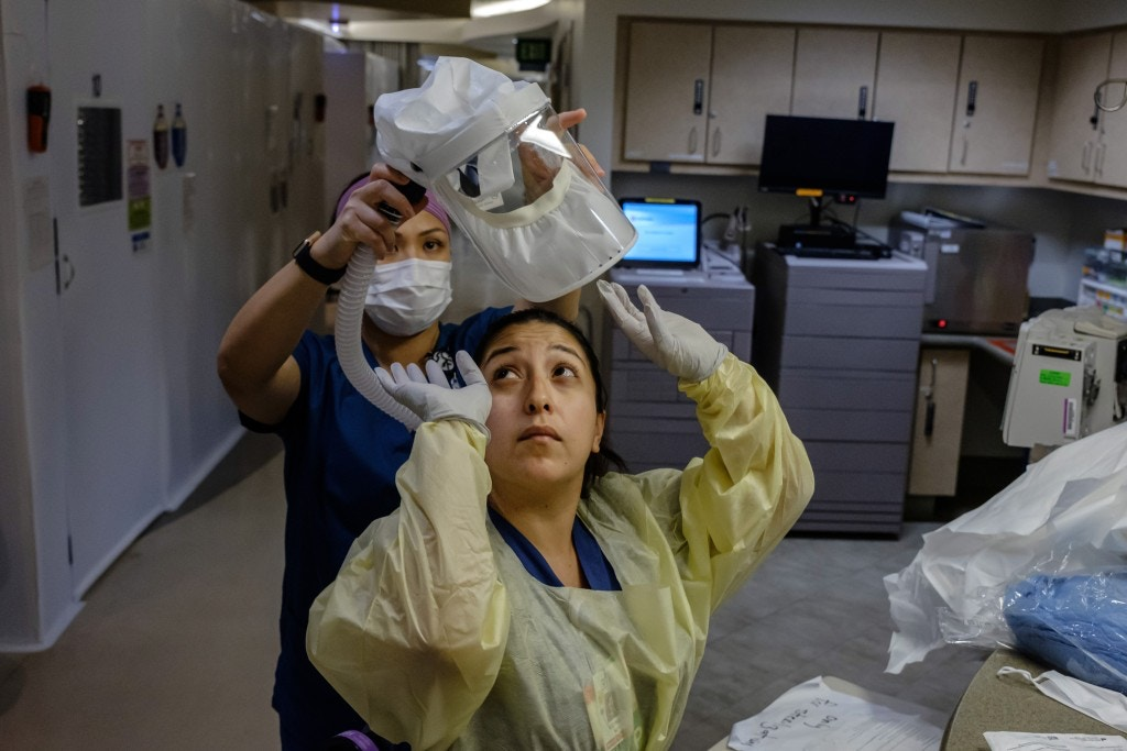 CHULA VISTA, CALIF. -- FRIDAY, APRIL 10, 2020: A nurse gets help putting on her personal protective equipment before heading into a negative pressure room to administer care for a COVID-19 patient, at Sharp Chula Vista Medical Center in Chula Vista, Calif., on April 10, 2020. (Marcus Yam / Los Angeles Times via Getty Images)