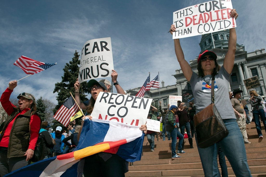"Demonstrators gather in front of the Colorado State Capitol building to protest coronavirus stay-at-home orders during a ""ReOpen Colorado"" rally in Denver, Colorado, on April 19, 2020. - Hundreds protested on April 18 in cities across America against coronavirus-related lockdowns -- with encouragement from President Donald Trump -- as resentment grows against the crippling economic cost of confinement. (Photo by Jason Connolly / AFP) (Photo by JASON CONNOLLY/AFP via Getty Images)"