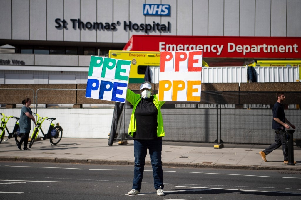 LONDON, ENGLAND - APRIL 07: A woman holds up a banner with 'PPE' painted on outside St Thomas' Hospital on April 07, 2020 in London, England. Prime Minister Boris Johnson was transferred to the intensive care unit at St Thomas' Hospital after his coronavirus symptoms worsened last night. (Photo by Justin Setterfield/Getty Images)