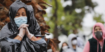 VAN NUYS, CALIFORNIA - APRIL 09: Juana Gomez, 50, from North Hollywood, wears a face mask and gloves, while using a trash bag to protect against the rain, as she waits in line to receive food at a Food Bank distribution for those in need as the coronavirus pandemic continues on April9, 2020 in Van Nuys, California. Organizers said they had distributed food for 1,500 families amid the spread of COVID-19.  (Photo by Mario Tama/Getty Images)