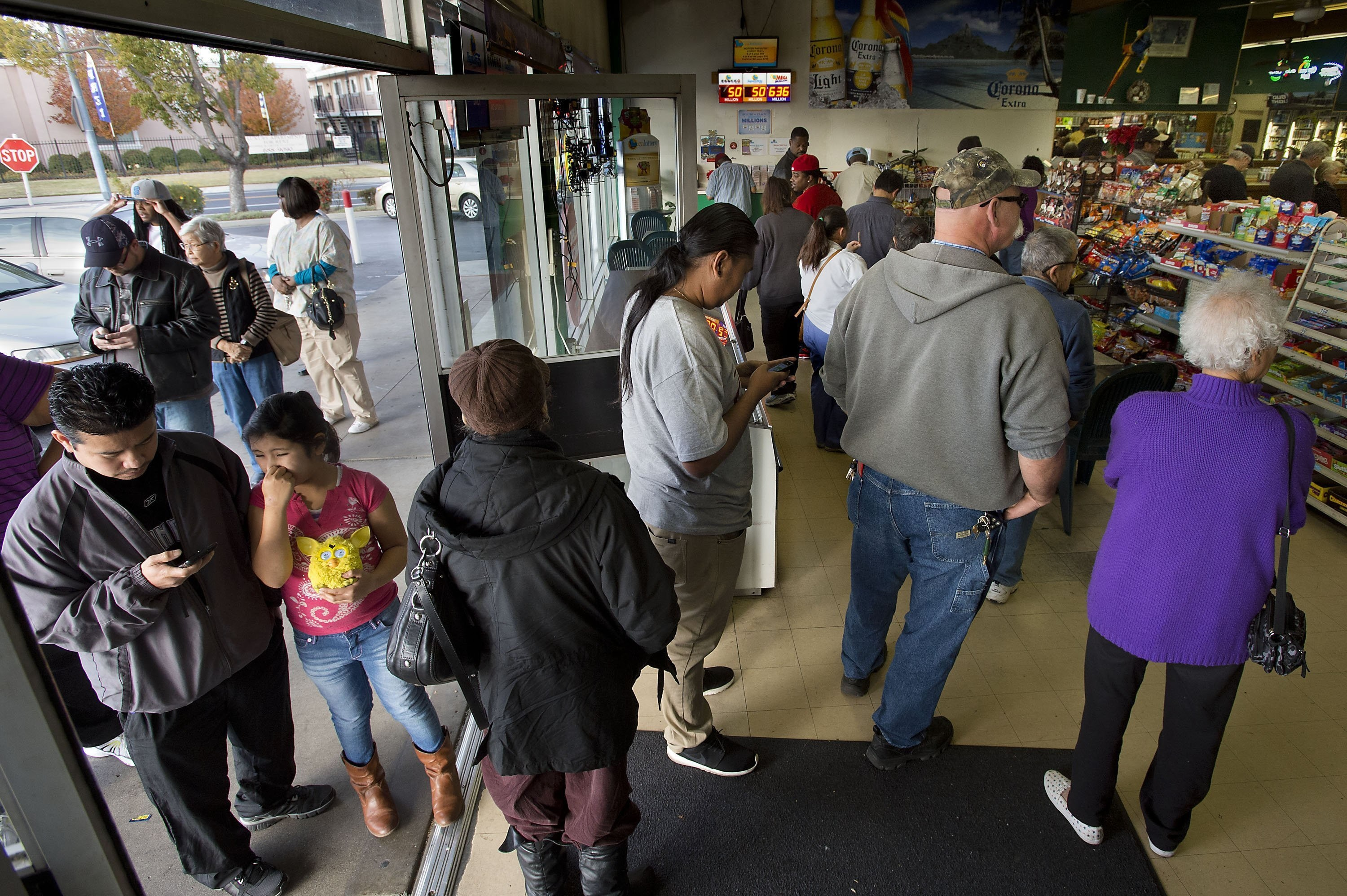 Patrons wait to buy Mega Millions lottery tickets at Lichines Liquor & Deli in Sacramento, Ca., on Tuesday, Dec. 17, 2013. The jackpot has soared to $636 million for Tuesday night's drawing. (Randall Benton/Sacramento Bee/Tribune News Service via Getty Images)