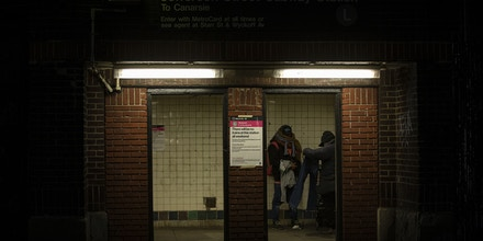 Two homeless men are seen in a subway entrance in Brooklyn, New York March 22, 2020, (Marshall Ritzel via AP)