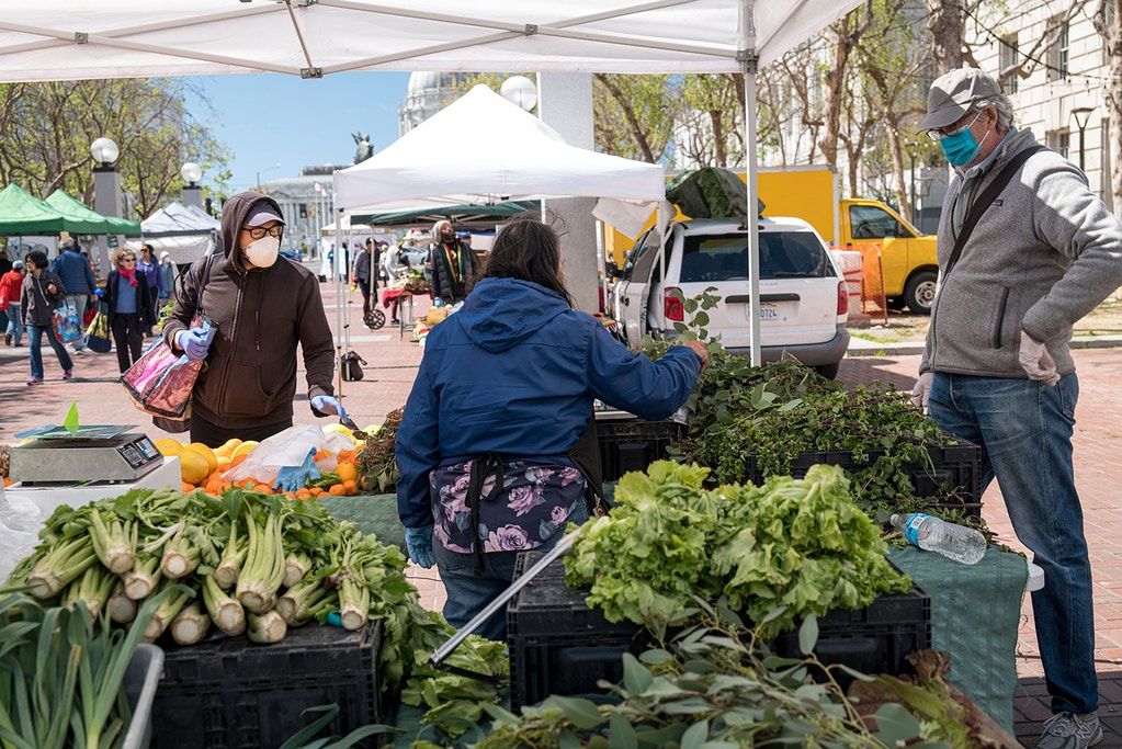 Shoppers wearing protective face masks and gloves browses produce at a farmers market in San Francisco, California, U.S., on Wednesday, March 25, 2020. Fearful of close-quarters in packed supermarkets marked by empty shelves, many shoppers have descended on farmers markets they rarely visited in the past. Photographer: David Paul Morris/Bloomberg via Getty Images