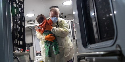 STAMFORD, CONNECTICUT - APRIL 04: (EDITORIAL USE ONLY)  Paramedic Randy Lilly, wearing personal protection equipment (PPE), carries a 10-month-old boy with fever after arriving by ambulance to Stamford Hospital on April 04, 2020 in Stamford, Connecticut. Fever is a common symptom of COVID-19, although cases with young children are relatively rare. The child's status is unknown. Stamford now has more than 1,000 confirmed coronavirus cases, the highest of any city in Connecticut. The majority of Stamford EMS calls are now for COVID-19 patients. (Photo by John Moore/Getty Images)