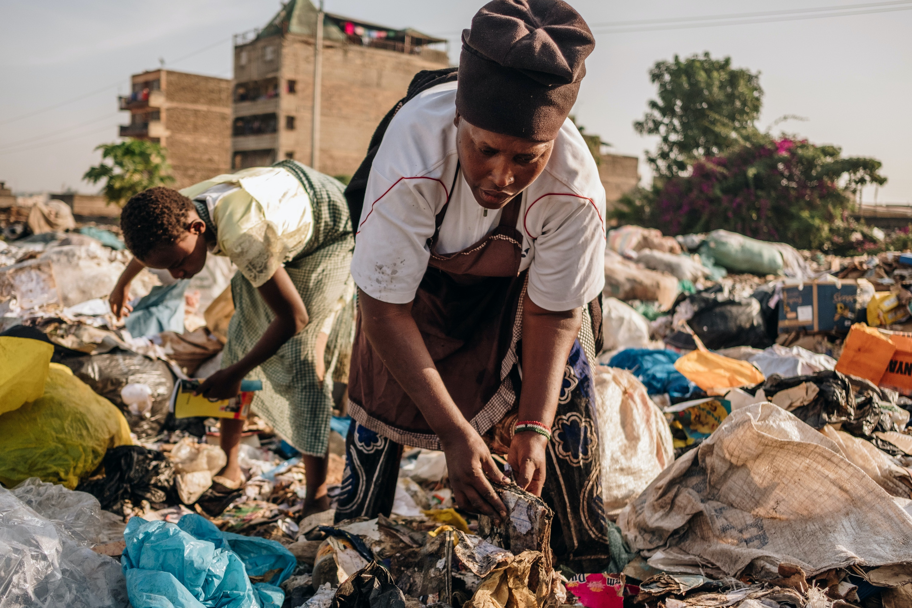 Miriam Nyambura and her 11-year-old niece, Rosemary, collect discarded cardboard boxes, paper, and plastic bottles at the Dandora dump on Feb. 29, 2020. Miriam picks an average of 20kgs of waste each day.