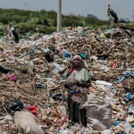 A woman takes a break from collecting waste to read the newspaper at the Dandora municipal dump site in Nairobi, Kenya, on Feb. 15, 2020.
