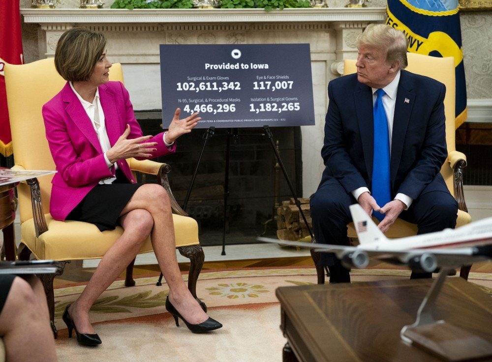 U.S. President Donald Trump listens as Kim Reynolds, governor of Iowa, left, speaks during a meeting in the Oval Office of the White House in Washington, D.C., U.S., on Wednesday, May 6, 2020. Trump fixed his course on reopening the nation for business, acknowledging that the move would cause more illness and death from the pandemic but insisting it's a cost he's willing to pay to get the economy back on track. Photographer: Doug Mills/The New York Times/Bloomberg