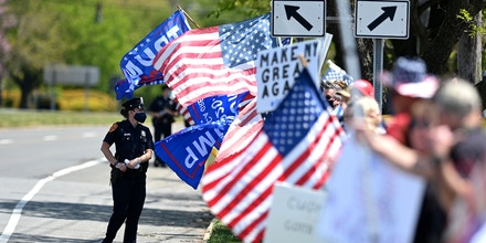 Protestors gather with US flags as they attend an
