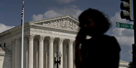 A pedestrian passes the U.S. Supreme Court in Washington, D.C., U.S., on Tuesday, July 9, 2019. At the end of its term, the Supreme Court agreed to hear President Donald Trump's bid to end deportation protections for hundreds of thousands of young undocumented immigrants, taking up a politically explosive issue likely to be resolved in the heat of next year's election campaign. Photographer: Andrew Harrer/Bloomberg via Getty Images