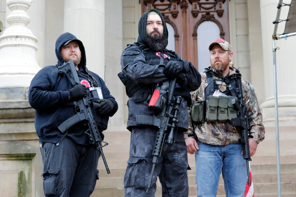 "Armed men take part in an ""American Patriot Rally,"" organized on April 30, 2020, by Michigan United for Liberty on the steps of the Michigan State Capitol in Lansing, demanding the reopening of businesses. (Photo by JEFF KOWALSKY / AFP) (Photo by JEFF KOWALSKY/AFP via Getty Images)"