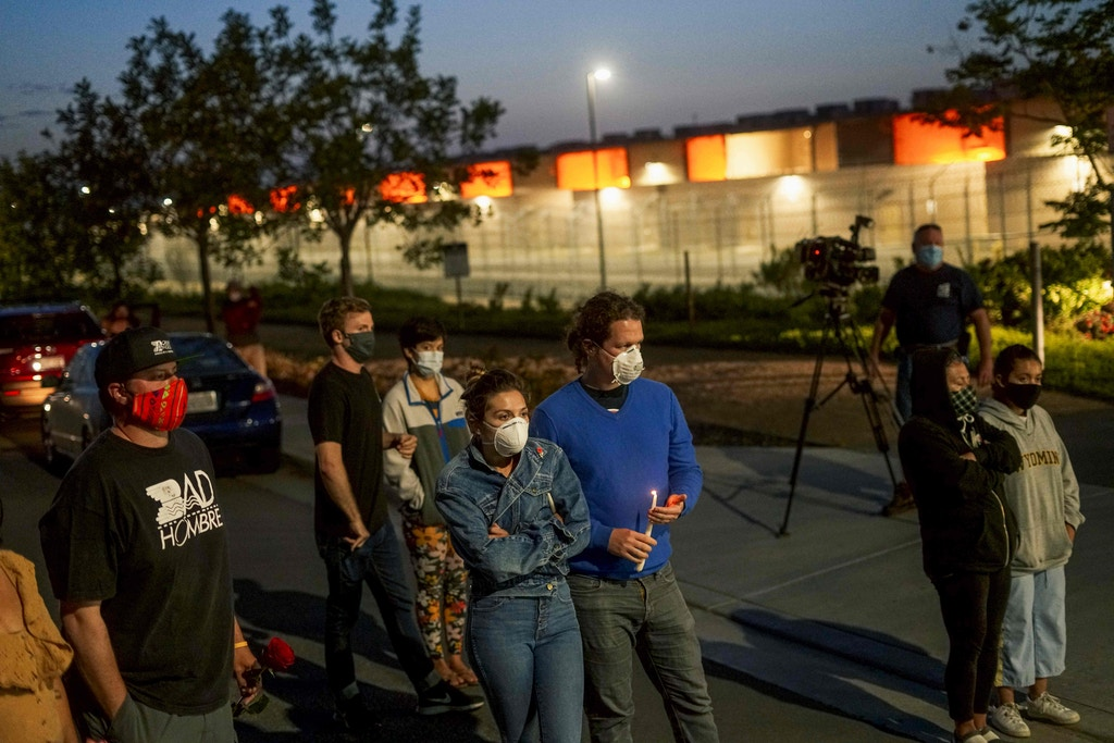 "Protesters stand outside Otay Mesa Detention Center during a ""Vigil for Carlos"" rally on May 9, 2020 in Otay Mesa, California. - The vigil was held to commemorate Carlos Ernesto Escobar Mejia, the first illegal immigrant who died of COVID-19 related symptoms while being held at the detention Center. (Photo by SANDY HUFFAKER / AFP) (Photo by SANDY HUFFAKER/AFP via Getty Images)"