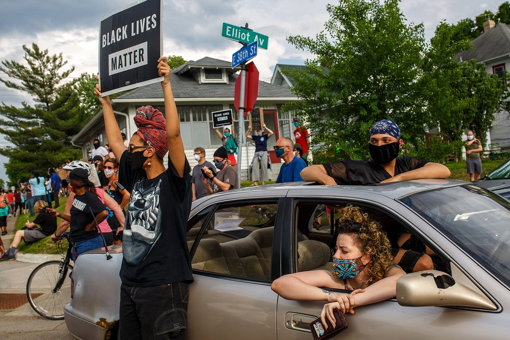 TOPSHOT - People hold signs and protest after a Minneapolis Police Department officer allegedly killed George Floyd, on May 26, 2020 in Minneapolis, Minnesota. - A video of a handcuffed black man dying while a Minneapolis officer knelt on his neck for more than five minutes sparked a fresh furor in the US over police treatment of African Americans Tuesday. Minneapolis Mayor Jacob Frey fired four police officers following the death in custody of George Floyd on Monday as the suspect was pressed shirtless onto a Minneapolis street, one officer's knee on his neck. (Photo by Kerem Yucel / AFP) (Photo by KEREM YUCEL/AFP via Getty Images)