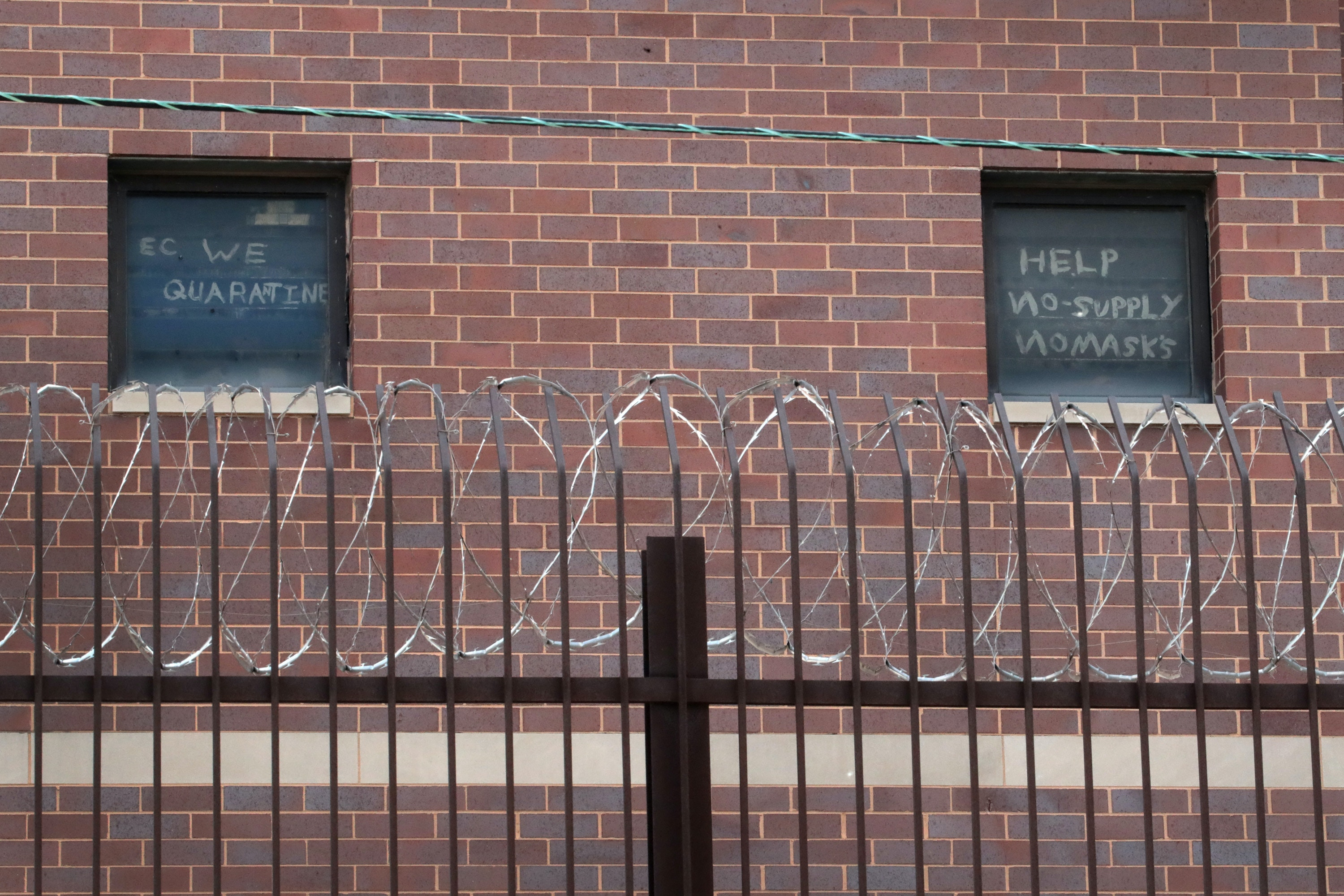 CHICAGO, ILLINOIS - APRIL 09: Signs pleading for help hang in windows at the Cook County jail complex on April 09, 2020 in Chicago, Illinois. With nearly 400 cases of COVID-19 having been diagnosed among the inmates and employees, the jail is nation's largest-known source of coronavirus infections. (Photo by Scott Olson/Getty Images)