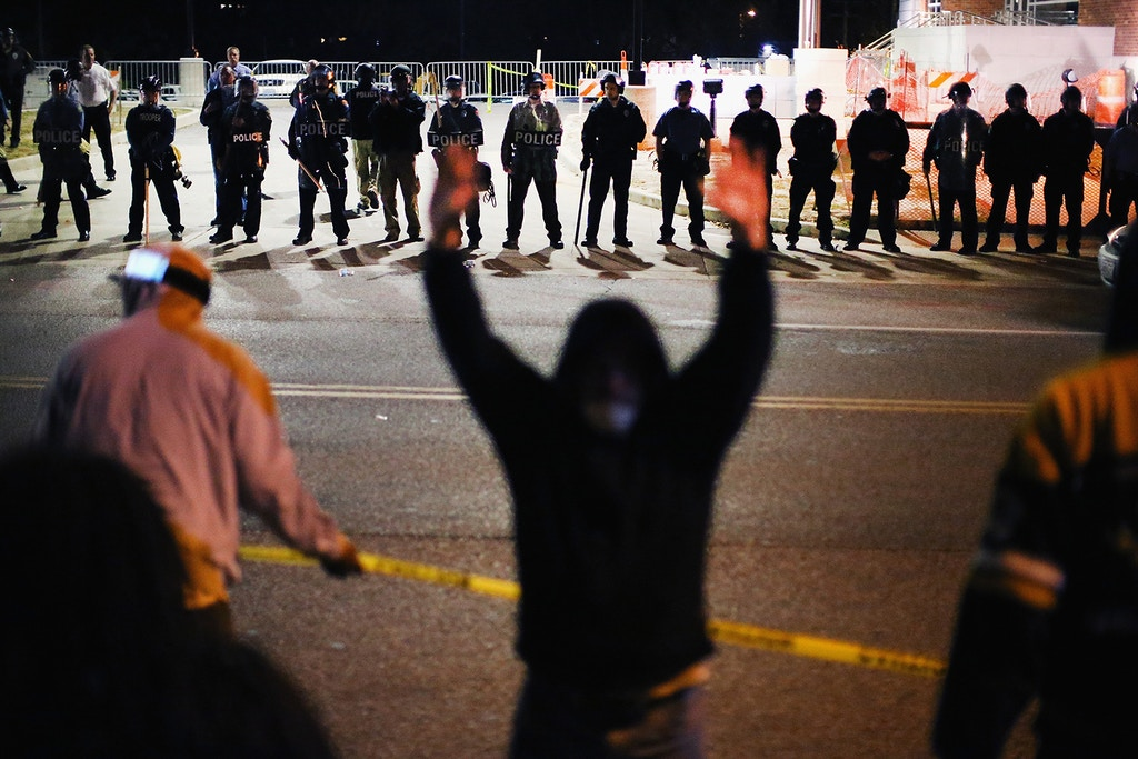 FERGUSON, MO - OCTOBER 22:  Police face off with demonstrators outside the police station as protests continue in the wake of 18-year-old Michael Brown's death on October 22, 2014 in Ferguson, Missouri. Several days of civil unrest followed the August 9 shooting death of Brown by Ferguson police officer Darren Wilson. Today's protest was scheduled to coincide with a day of action planned to take place nationwide to draw attention to police brutality.  (Photo by Scott Olson/Getty Images)