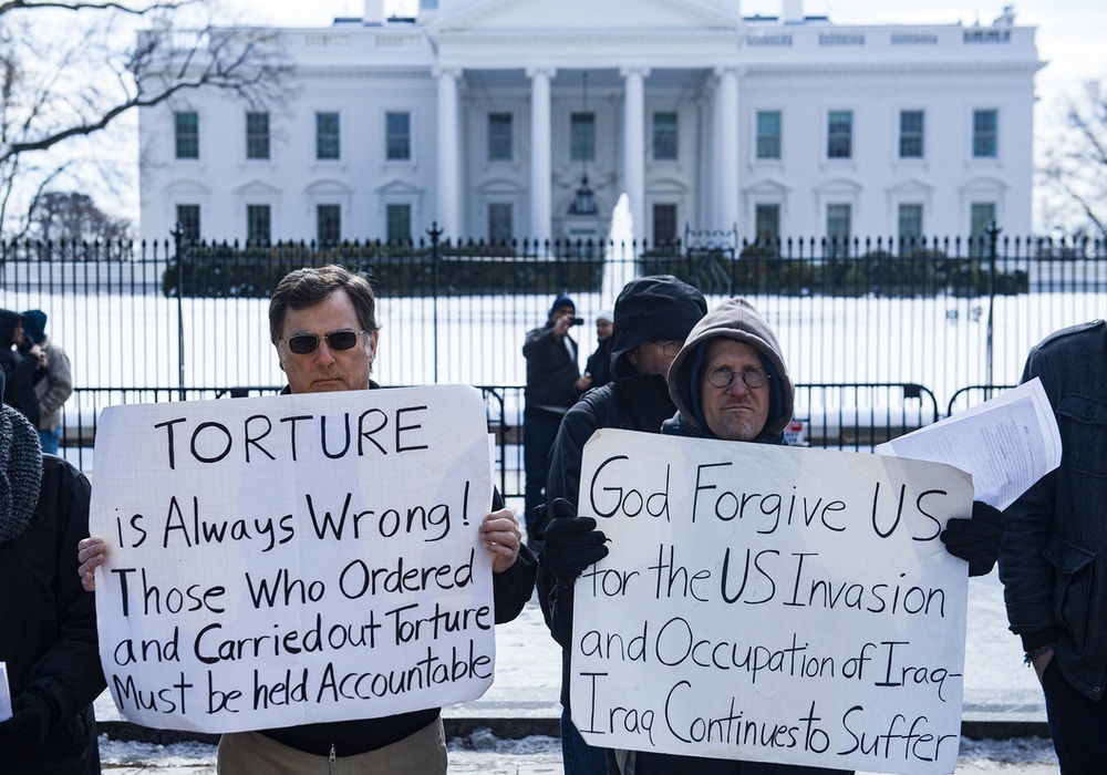 Protestors demonstrating against torture stand in front of the White House in Washington, DC, February 18, 2015. AFP PHOTO / SAUL LOEB        (Photo credit should read SAUL LOEB/AFP via Getty Images)