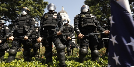 SACRAMENTO,CACHP officers wearing riot gear line the edge of the CA state capitol grouds after removing protesters on Friday, May 1, 2020. Over 1,500 people attending a rally at the capitol in Sacramento asking for the civil liberties and the opening of the economy, closed due to the coronavirus.   (Carolyn Cole/Los Angeles Times via Getty Images)