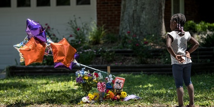 BRUNSWICK, GA - MAY 08: A young girl looks at a memorial for Ahmaud Arbery near where he was shot and killed May 8, 2020 in Brunswick, Georgia. Gregory McMichael and Travis McMichael were arrested the previous night and charged with murder relating to the February 23 shooting in the Satilla Shores neighborhood. (Photo by Sean Rayford/Getty Images)