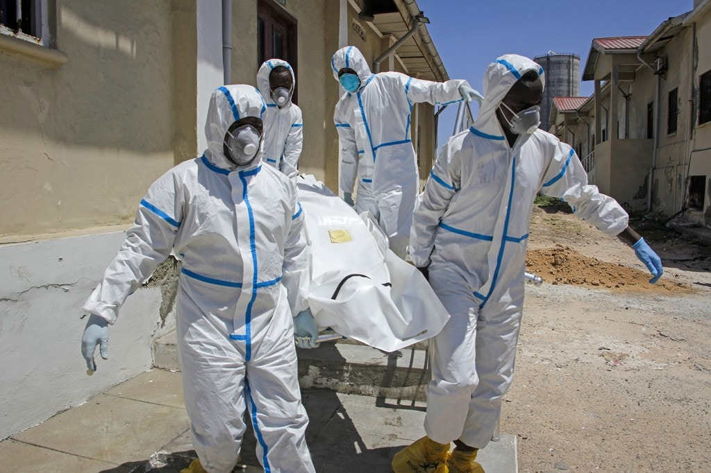 In this photo taken Wednesday, May, 13, 2020, medical workers in protective suits carry the body of Ibrahim Hassan, 56, before he is buried in Mogadishu, Somalia. His brother said he died of the coronavirus at the Martini Hospital. At the hospital, the main facility treating COVID-19 patients in Mogadishu, health care workers have received little training, and they have raised concerns about their personal safety. (AP Photo/Farah Abdi Warsameh)