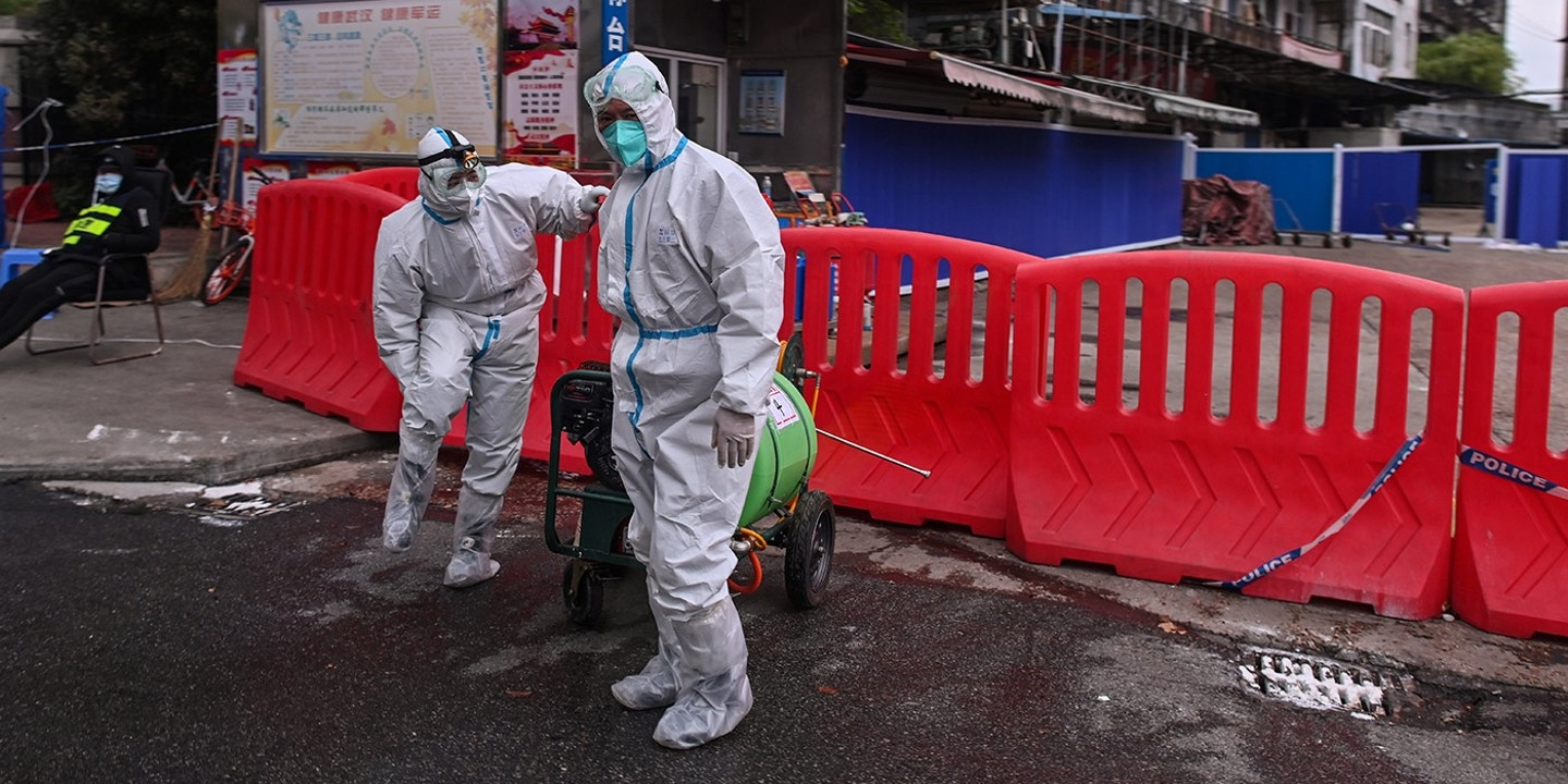 Workers wearing protective suit walk next to Huanan Seafood Wholesale Market in Wuhan, in China's central Hubei province on March 30, 2020, after travel restrictions into the city were eased following more than two months of lockdown due to the COVID-19 coronavirus outbreak. - Wuhan, the central Chinese city where the coronavirus first emerged last year, partly reopened on March 28 after more than two months of near total isolation for its population of 11 million. (Photo by Hector RETAMAL / AFP) (Photo by HECTOR RETAMAL/AFP via Getty Images)