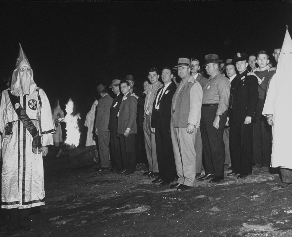 May 1946: The new Ku Klux Klan initiates, including several Atlanta police officers, standing near a burning cross during the initiation ceremony on Stone Mountain.  (Photo by Ed Clark/The LIFE Picture Collection via Getty Images)