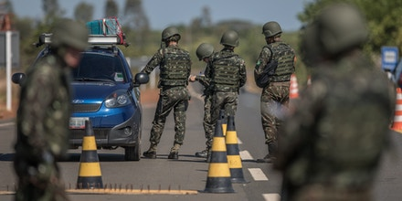 Members of the Brazilian Army check vehicles traveling along BR 174 highway, often used by Venezuelans seeking shelter in Brazil, in Pacaraima, Roraima state, Brazil, on Tuesday, Feb. 20, 2018.