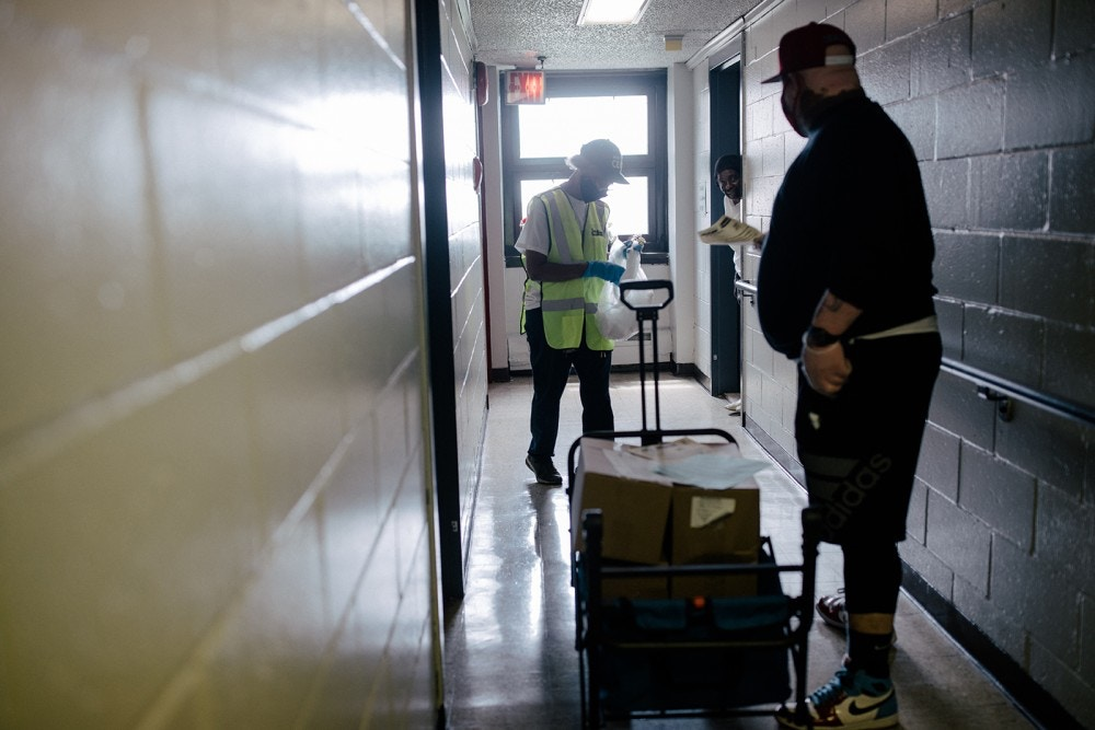 Valerie Woodford, a retired correctional officer, senior citizen, and active member of the Community Emergency Response Team (CERT), leads an employee of the nonprofit Millennium Development on the food drops for residents of the 8th floor in building 77 of the Vandalia Avenue Houses, New York City, New York, U.S., May 29, 2020. José A. Alvarado Jr. for The Intercept