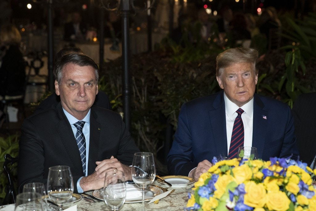 FILE - In this March 7, 2020, file photo President Donald Trump is seated before a dinner with Brazilian President Jair Bolsonaro, left, at Mar-a-Lago in Palm Beach, Fla. Bolsonaro's communications director, Fábio Wajngarten, tested positive just days after traveling with Bolsonaro to a meeting with Trump and senior aides in Florida. (AP Photo/Alex Brandon, File)