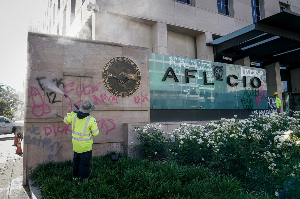 WASHINGTON, DC - JUNE 01: Workers clean graffiti off of an entrance sign to the AFL-CIO headquarters that was vandalized during overnight unrest, June 1, 2020 in Washington, DC. Protests and riots continue across American following the death of George Floyd, who died after being restrained by Minneapolis police officer Derek Chauvin. Chauvin, 44, was charged last Friday with third-degree murder and second-degree manslaughter. (Photo by Drew Angerer/Getty Images)