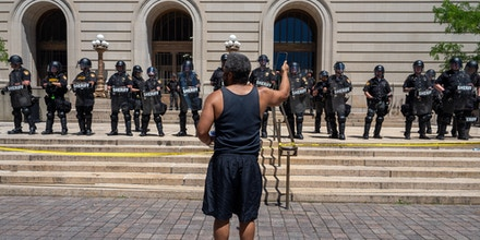 A man reads from his phone towards Hamilton County Sheriff deputies as demonstrators rally at the Hamilton County Courthouse to protest the murder of George Floyd, Monday, June 1, 2020, in Cincinnati, Ohio, United States. (Photo by Jason Whitman/NurPhoto via Getty Images)