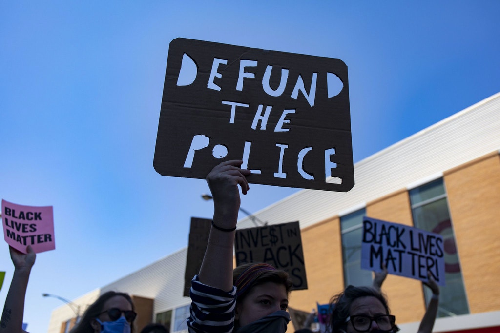 "Protesters carry a ""Defund the Police"" sign on West Division Street during the March of Justice from Union Park to Cabrini-Green on Saturday, June 6, 2020 in Chicago to demand police accountability. (Brian Cassella/Chicago Tribune/Tribune News Service via Getty Images)"