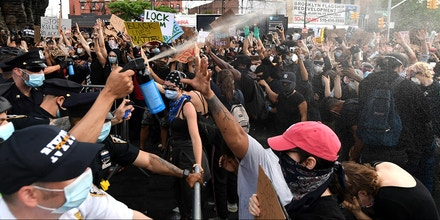 NEW YORK, NEW YORK - MAY 29:  NYPD Officers spray mace into the crowd of protesters gathered at Barclays Center to protest the recent killing of George Floyd on May 29, 2020 in Brooklyn in New York City.  Demonstrations are being held across the US after George Floyd died in police custody on May 25th. (Photo by Kevin Mazur/Getty Images)