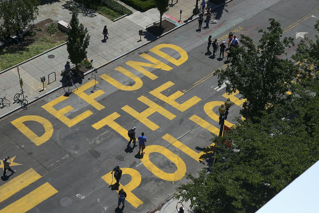 "WASHINGTON, DC - JUNE 08: People walk down 16th street after ""Defund The Police"" was painted on the street near the White House on June 08, 2020 in Washington, DC. After days of protests in DC over the death of George Floyd, DC Mayor Muriel Bowser has renamed that section of 16th street ""Black Lives Matter Plaza"". (Photo by Tasos Katopodis/Getty Images)"