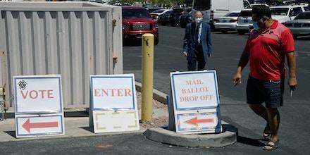 Pessoas caminham seguindo os cartazes enquanto se dirigem ao Departamento Eleitoral do Condado de Clark, que serve como ponto de votação principal nas eleições e como centro de votação presencial em meio à pandemia de coronavírus em 9 de junho de 2020, em North Las Vegas, Nevada.