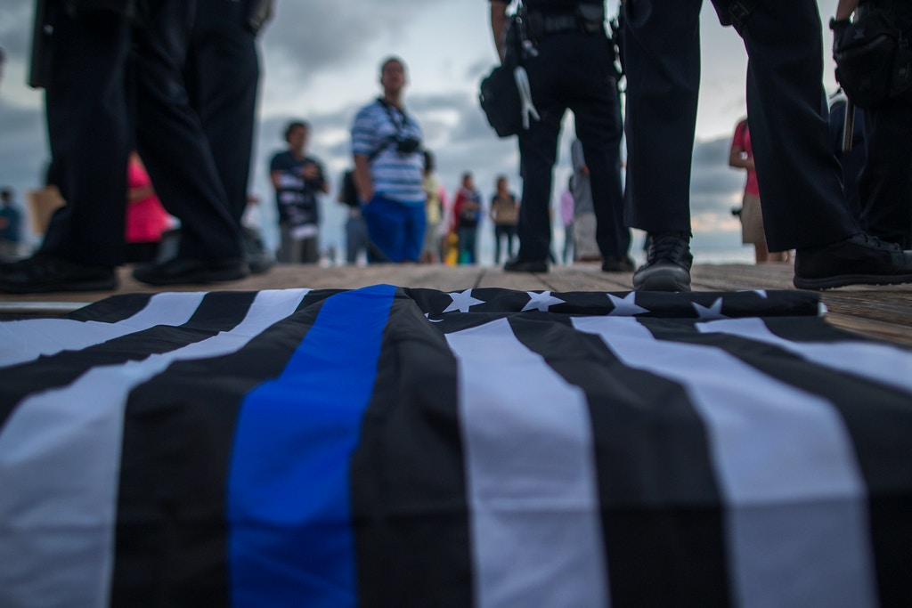LAGUNA BEACH, CA - AUGUST 20: A flag with the thin blue line, which is used to honor the fallen and the courage of police officers, lies on the boardwalk near the feet of police keeping demonstrators and counter demonstrators apart during an 'America First' demonstration on August 20, 2017 in Laguna Beach, California. Organizers of the rally describe it as a vigil for victims of illegal immigrants and refugees. Opponents say the demonstration is steeped in racism.  (Photo by David McNew/Getty Images)